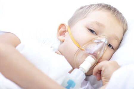 boy with an inhaler mask - respiratory problems in asthma. a boy with an inhaler mask lies in bed and breathes adrenaline. healthcare concept and sick child, coronavirus, bronchitis, pneumonia