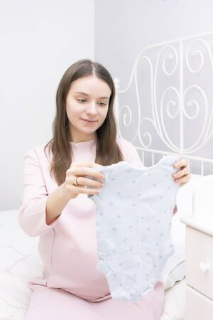 pregnant girl looks at things for a newborn. expectation of baby, motherhood. vertical photo