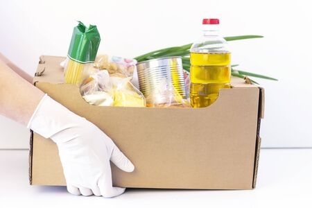 donation box. in hands in rubber gloves is a cardboard box with food on a white background.