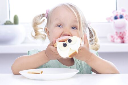 blonde girl eating a sandwich at the table, on a light background.