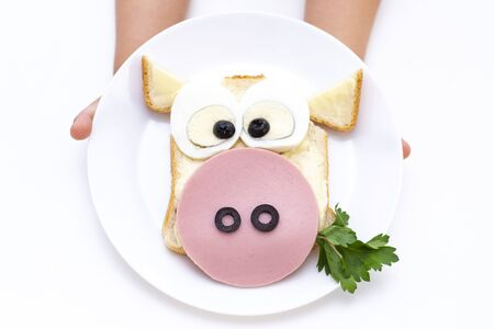 sandwich bull.  child hands have a white plate with a sandwich for breakfast or lunch. Standard-Bild