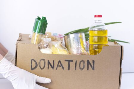 donation box. in hands in rubber gloves is a cardboard box with the inscription donation with food on a white background.