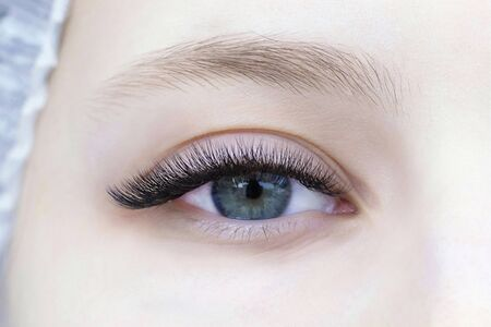 Eyelash extensions. Close-up of eye with extended eyelashes of a white girl
