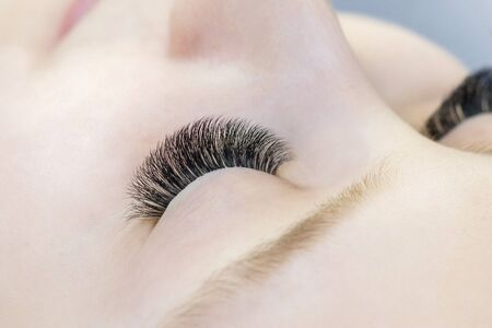 Eyelash extensions. Closeup of eyes with extended eyelashes and without extended eyelashes, white girl. before and after