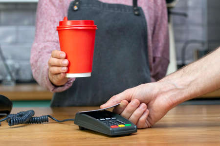 Takeaway coffee. barista holds out a red paper glass with a drink, the buyer pays with a card 스톡 콘텐츠