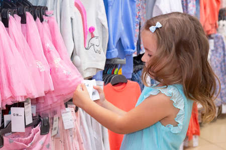 Girl chooses clothes in a clothing store.