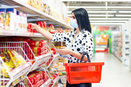 girl in a protective mask makes purchases in the supermarket. Girl holding a grocery basket in her hands and chooses products on the shelf