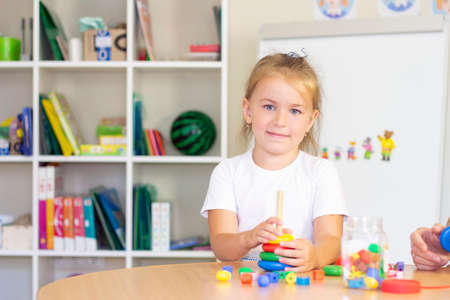 developmental and speech therapy classes with a child-girl. Speech therapy exercises and games with a colored pyramid