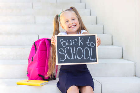 schoolgirl sits on the steps of the school, school backpack. Holds a sign in his hands with the inscription back to school. blurry face