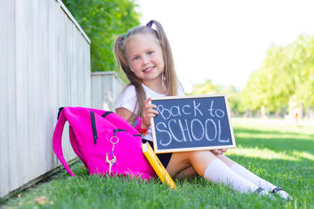 schoolgirl sits on the grass, school backpack. Holds a sign in his hands with the inscription back to school
