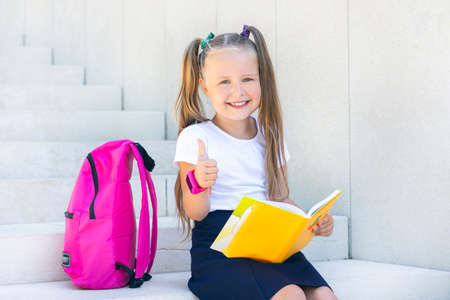 schoolgirl sits with a backpack and a textbook and smiles.