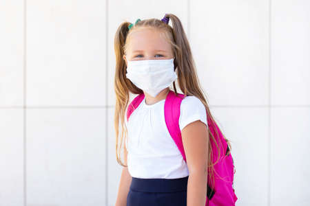 schoolgirl stands with a backpack in a protective medical mask