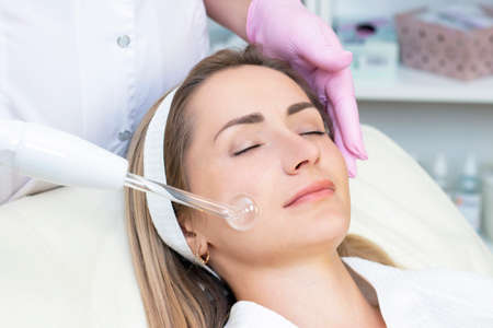Cosmetologist performs a pulse current procedure for the face of a young woman. close Archivio Fotografico