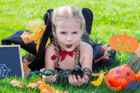 girl in a witch costume for the Halloween holiday. Placard with the inscription: Halloween. Happy girl lies on the grass with spiders