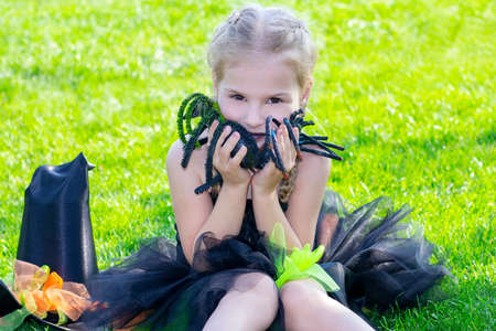 girl in a witch costume for the Halloween holiday. Happy girl sitting on the grass with spiders