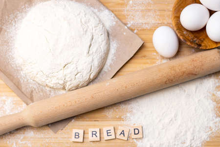 Preparation of dough for home pancakes for Breakfast. Ingredients on the table wheat flour, eggs. inscription bread Stok Fotoğraf