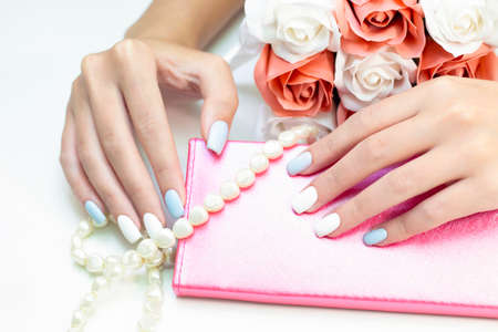 Stylish fashionable female manicure. Beautiful hands of a young woman on a background of flowers and beads from pearls