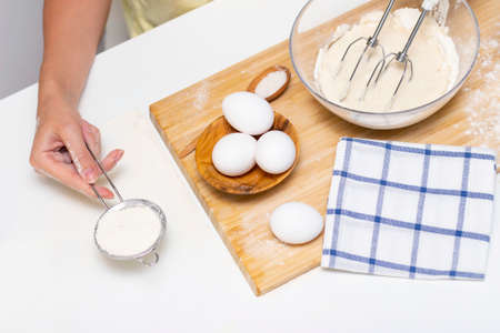 female hands hold a mixer for mixing dough