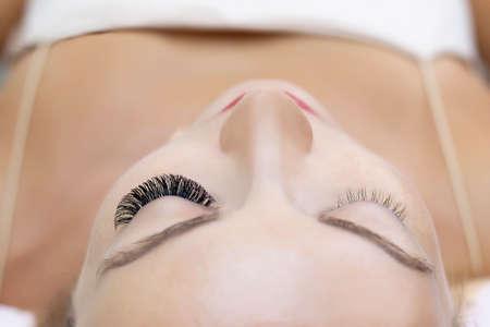 Eyelash extension procedure. Woman eye with long eyelashes. Close up