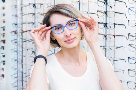 young woman in optic store choosing new glasses with optician. glasses in the store of optics. A woman chooses glasses. Emotions. Ophthalmology. Stock Photo