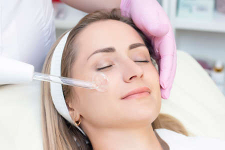 Cosmetologist performs a pulse current procedure for the face of a young woman.
