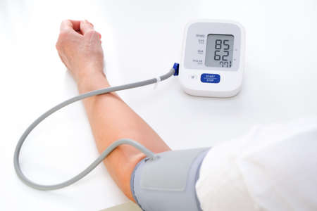 Adult woman measures blood pressure, white background. arterial hypotension.