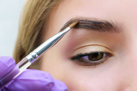 Young woman shaping eyebrows with brush, close up