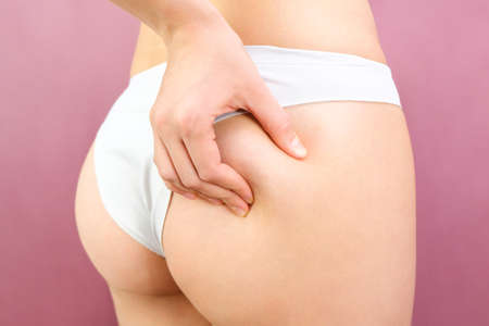 Close up view of a slender woman in lingerie on a pink background. Cellulite problem concept Standard-Bild