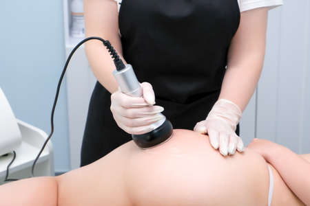 Vacuum massage device. Vacuum massage of the and legs. Anti cellulite body correction treatment. Loss weight apparatus. young woman and doctor at medicine salon. Foto de archivo