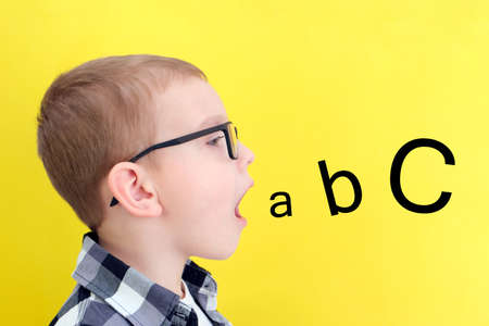 speech therapy. Toddler boy says open mouth with letters. Classes with a speech therapist. boy on isolated yellow background
