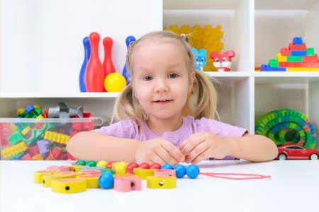 speech therapy, the development of fine motor skills. Toddler girl is stringing beads on a string. Reklamní fotografie