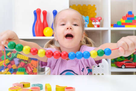 speech therapy, the development of fine motor skills. Toddler girl is stringing beads on a string. Foto de archivo