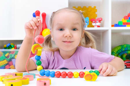 speech therapy, the development of fine motor skills. Toddler girl is stringing beads on a string. Stock Photo