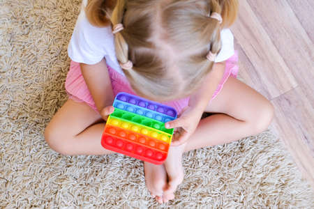 Girl play with pop it sensory toy. Stress and anxiety relief. Trendy silicon fidgeting game for stressed children