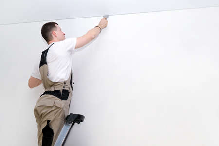 worker installs a stretch ceiling. Construction and renovation concept