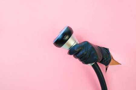 vacuum hardware massage on a pink background. hand in a black glove with an apparatus. Cellulite solution and weight loss. copy space