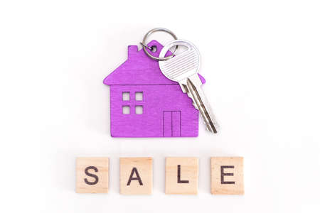 figure of a mini house of purple color with keys on an isolated white background. Wooden letters inscription sale Foto de archivo