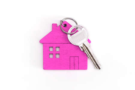 figure of a mini house of pink color with keys on an isolated white background. Foto de archivo