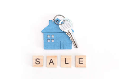 Blue mini house figure with keys on an isolated white background. Wooden letters inscription sale