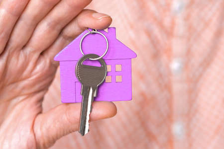 figure of a purple mini house with the keys are in the hand of a man on a beige background