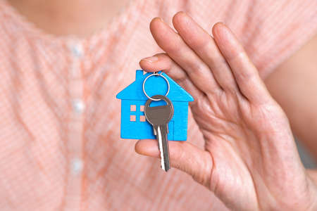 figure of a blue mini house with the keys are in the hand of a person