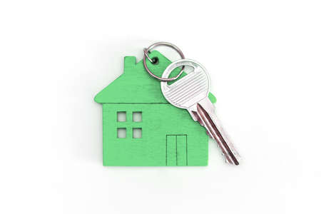 Figure of a mini house of green color with keys on an isolated white background. Foto de archivo