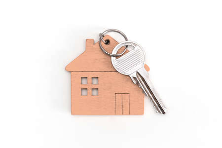 Figure of a mini house in beige color with keys on an isolated white background.