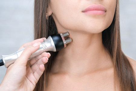 Hardware cosmetology. Young woman getting RF neck lifting procedure in beauty salon. Foto de archivo