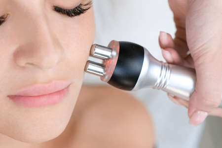Hardware cosmetology. Young woman getting RF face lifting procedure in beauty salon. Foto de archivo