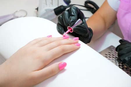 young woman gets a manicure in the salon. applying shellac to the nails. pink color Foto de archivo