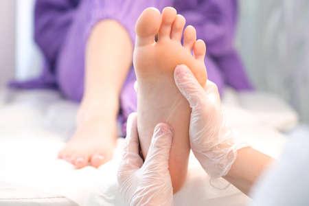 medical pedicure. foot massage with hands in transparent gloves. Foto de archivo