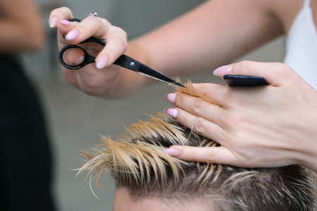 hairdresser cuts the hair of a young man with blond dyed hair with scissors in a beauty salon. Professional hair care.