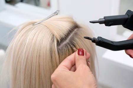hairdresser makes hair extensions to a young blonde girl in a beauty salon. Professional hair care.