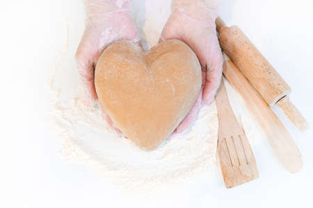 female hands holding heart shaped dough top view. Baking ingredients on white table